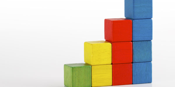 Toys blocks as step stair, multicolor wooden ladder building bricks over white background.