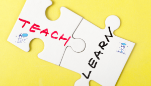 "two puzzle pieces on a yellow background. the first puzzle piece says ""teach"", the second ""learn"""