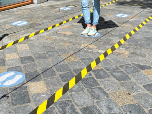 View on feet of one person between do not cross tapes and blue markings to keep distance at shop entrance in corona crisis