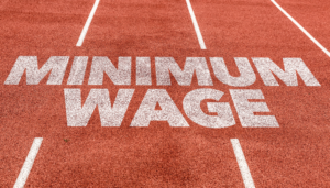 """pink sports track with the words """"minimum wage"""" written on the ground"""