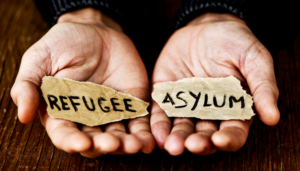 "tho hands holding the words ""refugee"" and ""asylum"""