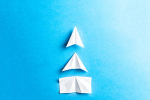 Three stages paper plane origami on a blue background