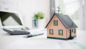 a house model, a calculator, a pen and some documents