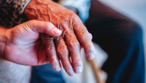 a younger hand holding and older person's hand