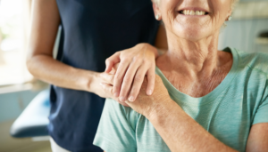 a young woman has put her hand on the shoulder of an elderly lady